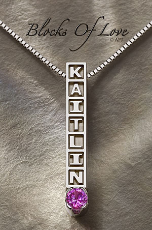 Blocks of Love pendants are custom created with raised lettering in square blocks reminiscent of the children's wooden building blocks, and includes a 3.5mm birthstone