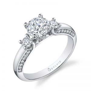 Modern three stone engagement ring with diamonds set in the side of the shank