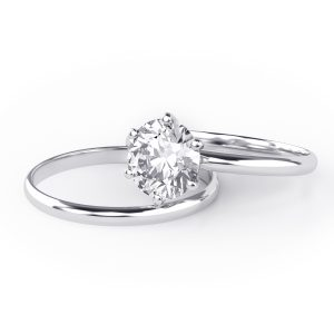 Clean white gold diamond engagement ring and wedding band that have been rhodium plated