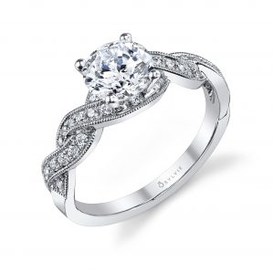 A white gold diamond engagement ring from the Sylvie Collection featuring a large center diamond and a weaving diamond shank with milgrain accents