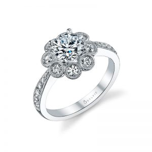 A white gold diamond engagement ring with eight bezel set diamond around a center stone