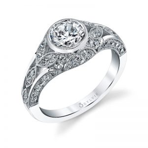 A vintage style engagement ring from the Sylvie Collection featuring a bezel set center stone and milgrain accents