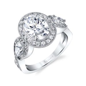 A white gold diamond engagement ring featuring a milgrain accented triple halo, three-stone design from the Sylvie Collection