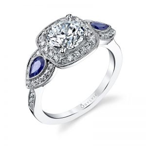 A white gold diamond three-stone halo engagement ring from the Sylvie Collection with large pear shaped sapphires on either side of the center stone