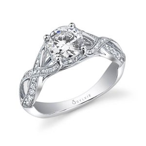 A white gold diamond engagement ring from the Sylvie Collection featuring a round diamond in the center and a twisting split shank with diamonds and milgrain accents