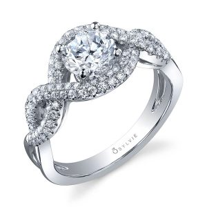 A white gold diamond engagement ring from the Sylvie Collection featuring swirling diamond shank and a round diamond